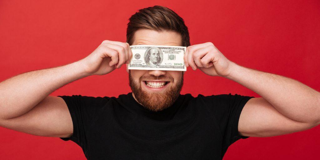 Homem segurando dinheiro sorrindo coaching financeiro